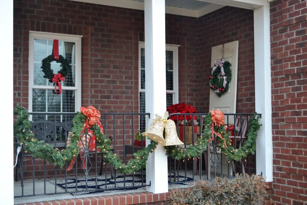 This Christmas Porch is so cute! I love the garland and old door with the wreath!