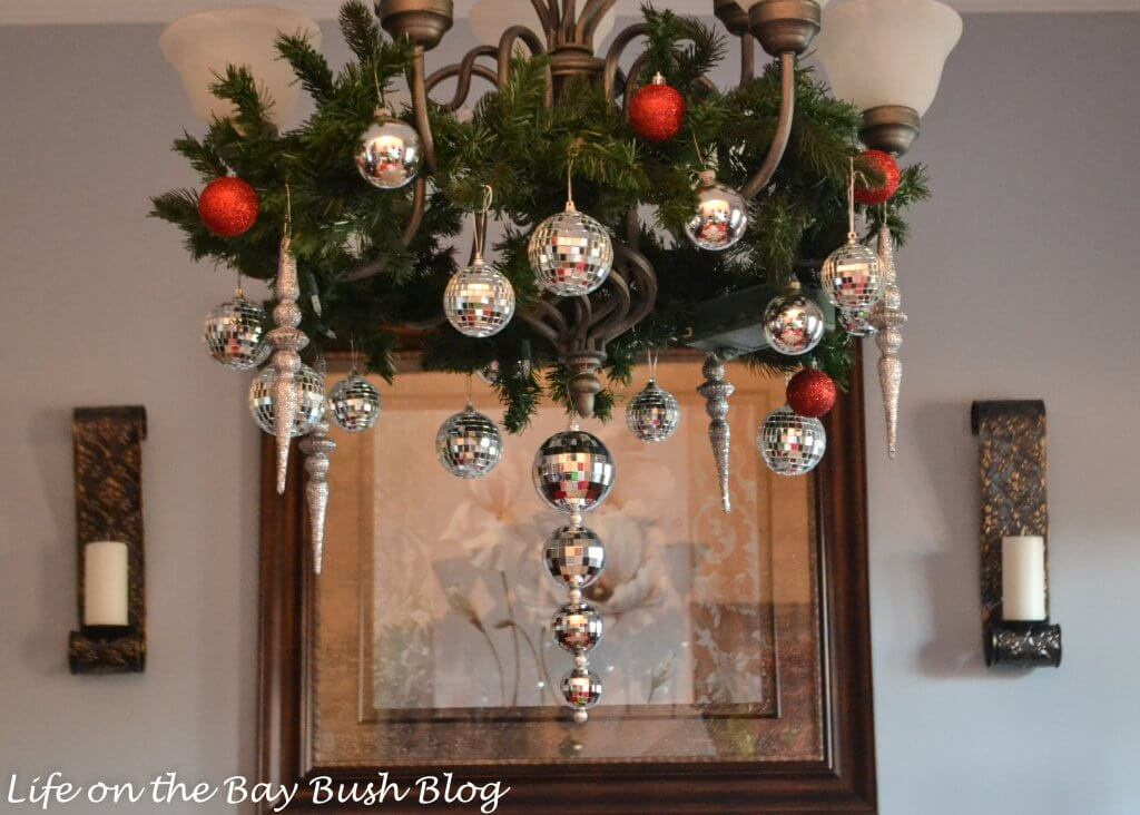 Christmas decorations on light fixture in a formal dining room