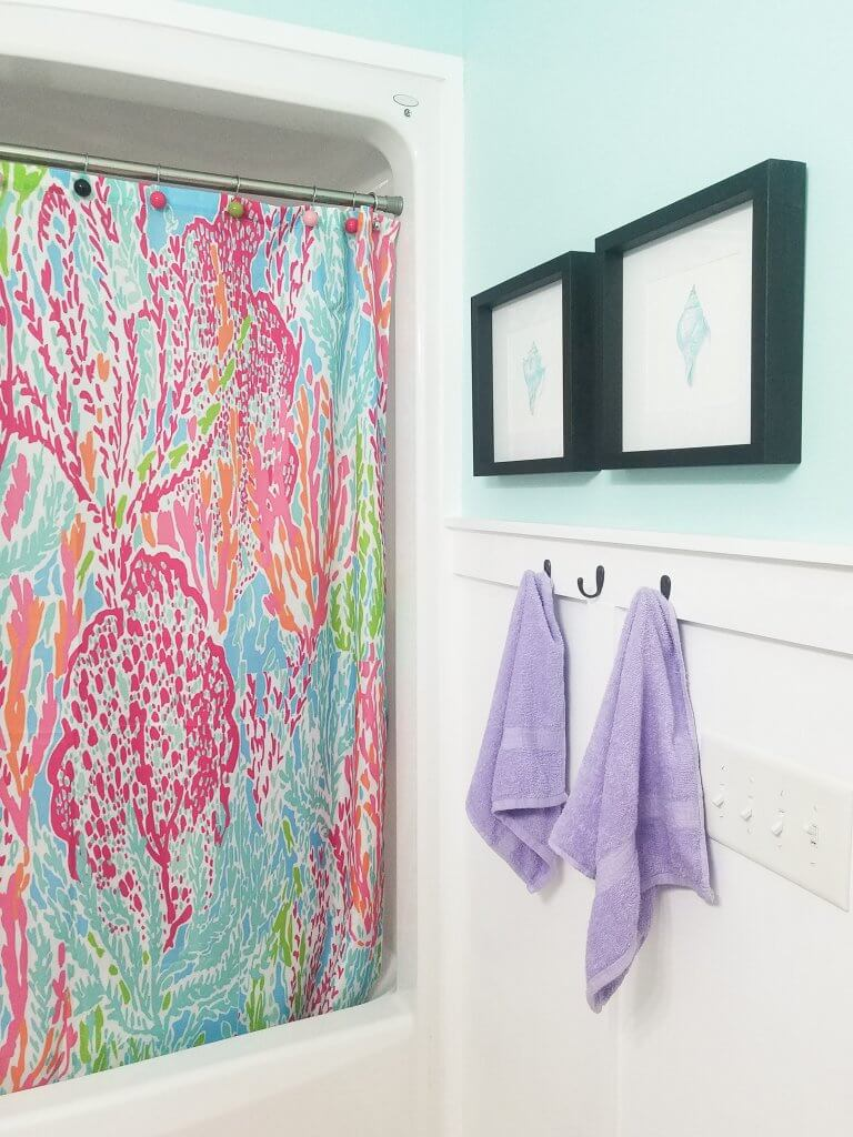 Love this coastal Lilly Pulitzer inspired bathroom makeover. The board and batten adds a fun coastal charm! Life on the Bay Bush#lillypulitzer #lillybathroom #bathroommakeover #boardandbattenbath #boardandbatten